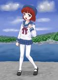 入り江の街を背にポーズをとる少女