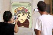 修復された絵を見学している人たち